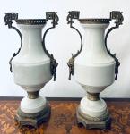 Magnífico Par de Ânforas em porcelana europeia, na cor branca, guarnecidas em bronze, decoradas com leões em suas laterais, base e adereços em bronze. Med. Alt. 55 cm.