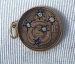 Antigo pingente feito a partir de moeda do império Brasileiro de 10 reis datada de 1888 com incrustação de 5 mínimos brilhantes representando a constelação do Cruzeiro do Sul fixado em aro de ouro, medindo 2 cm de diâmetro.