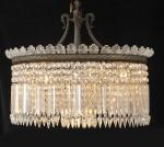 BACCARAT - Magnífico lustre de cristal francês, modelo Lady Crinoline, projetado pelo design francês Jean-Marc Gady para a Baccarat em 1895. Formato oval, com longos pingentes facetados dispostos em cascata e várias correntes de contas lapidadas, coroado por palmas. Medidas: comprimento 84 cm., altura só do corpo 40 cm, altura com estrutura de bronze 93 cm, profundidade 56 cm. Acompanha nota fiscal da Cristalleries de Baccarat - Paris, adquirido em 16/03/1951. Um pingente com colado, e alguns pequenos bicados.
