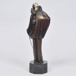 """ROLAND PARIS (França 1894-1945). """"Pierrot"""", escultura Art Deco circa 1910, em bronze pintado e marfim. Base em mármore negro rajado gravada Roland Paris.  Alt.34 cm."""