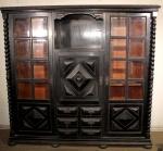 Antiga biblioteca no estilo Manoelino em madeira nobre ebanizada, portas laterais com placas de vidro bisotado. Medindo 152 x 170 x 47 cm. Apresenta prateleiras reguláveis. Apresenta desgastes na pintura.