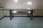 Mesa de jantar com espesso tampo de cristal de 20 mm, moderna base de madeira revestida de aço inox, com desgastes. Medida 220 x 110 cm.