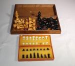 Dois jogos de xadrez, sendo um em caixa de madeira, completo, outro de menor tamanho em plástico, faltando 1 peça.