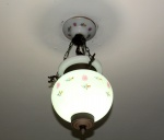 Lampião de vidro opalinado e pintado, estrutura de metal, terminação superior com quebrado. Medida 55 x 29 cm.