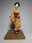 Estatueta representando gueixa, estrutura em algodão, rosto, pés e mãos em biscuit, roupa em tecido policromado, base em madeira. Alt. 45cm.