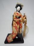 Estatueta representando gueixa, estrutura em algodão, rosto, pés e mãos em biscuit, roupa em tecido policromado. Alt. 31cm.