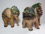 Duas esculturas representando elefantes indianos em cerâmica patinada, ricamente ornamentado com pedras e aplicações em metal dourado. Alts. 23cm.
