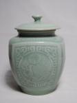 Potiche em cerâmica vitrificada de verde Celadon, ornamentado em suave alto relevo com flores, folhagens e geométricos característicos. Marcado com selo no fundo. Alt. 21cm.
