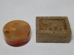Duas caixas: a) Pedra sabão, tampa com treliças e elefante esculpido, dobradiças de metal. 4,5 x 10,5 x 7,5cm. b) Pedra brasileira polida. Alt. 3,5 x Diam.8cm.