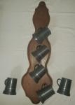 Seis canecas em estanho penduradas em placa de madeira com suportes (faltam 2). Canecas com amassados. Marcas do fabricante. Placa 81 x 25cm.