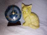 Duas peças: a) Gato em porcelana. Alt. 13cm. b) Relógio de mesa, mostrador em pedra brasileira, números em metal dourado, máquina à pilha. Alt. 11cm.