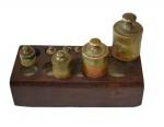 Base de madeira com 7 (sete) pesos de bronze para balança antiga. VEJA FOTO EXTRA. Apresenta falta de alguns pesos.