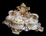 Antigo tinteiro Vieux Paris em porcelana moldada com acantos, conchas, volutas, máscaras e grifos, ricamente decorado a ouro. Apresenta falta na parte superior e uma das asas e ponta da outra dos grifos, possivelmente existia algum elemento que era encaixado na parte superior. Alt. 15 cm x 33 cm x 13 cm.