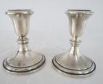 Par de castiçais em prata  STERLING com enchimento interno, marcada. Peso total 866 gramas. Med. 12 x 9,5 cm diâmetro. Haste com pequenas mossas.