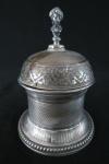 PRATA- Campainha de balcão á corda- cerca de 1930, em prata contrastada, ricamente cinzelada, parte superior com busto feminino para acionar a campainha. Marcas do tempo. Med. 11 cm alt x 8 cm diâmetro. Peso total 300 gramas.