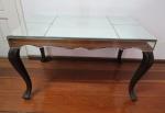 Belíssima mesa de centro com tampo e saia espelhado apoiada sobre quatro pés recurvos com entalhe na forma de palma. Med.: 52 x84x 47cm.