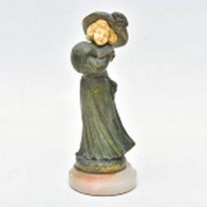 E. BERNOUD -  Estatueta de bronze.e marfim, menina com chapéu e roupa de inverno. Altura 17.5 cm.