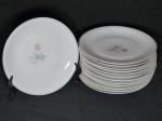 Treze pratos para sobremesa em porcelana nacional branca, borda filetada à ouro, centro aplicado com pinturas de rosas, 4 apresentam bicados, marcadas RENNER. Diam. 18cm