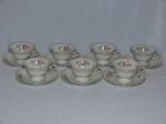 KPM - Sete xícaras e pires para café em porcelana polonesa branca, borda filetada a ouro, detalhes de acantos moldados na pasta, decoração de arranjos florais policromados. 4 x 12cm.