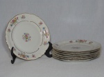 KPM - Sete pratos para sobremesa em porcelana polonesa branca, borda filetada a ouro, detalhes de acantos moldados na pasta, decoração de arranjos florais policromados. Diam. 17cm
