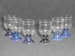 Seis taças para água em vidro translúcido com base em azul. Uma com base preta. Alt. 12cm.