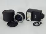 Dois acessórios para fotografia: a) Tele converter 2x to fit para câmeras minolta. 5 x 5cm. Acondicionada em capa de couro. b) Flash National modelo PE-201A, funcionamento desconhecido. 10 x 6 x 5cm.