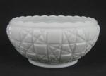 Bowl em milk glass decorado com trabalhos de sulcos em baixo relevo, formando geométricos. Borda com ondulações. Med. 10,5x21,5cm.