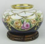 Cachepot em porcelana policromada e decorada com pintura floral e belos trabalhos em dourado com guirlandas, laços de fita e frisos. Med. 14,5x20,5 cm.