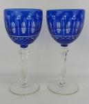 Par de taças em cristal europeu, de coleção, na tonalidade doublet azul e translúcida, lapidadas em olivas e frisos bisotados. Hastes sextavadas. Alts. 20cm.