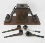 Caixa para cachimbos em madeira, contendo ao centro recipiente para fumo e em duas laterais  opostas, suporte para cachimbos. Acompanham 10 cachimbos de diversas procedências. Med. caixa 16,5x32x13cm.