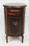 Criado mudo, formato circular, em madeira com marqueterie, formado por 1 gavetinha sobre 1 banda de porta. Guarnições em bronze com trabalhos em relevo. Med. 64x42cm.