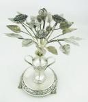 Paliteiro de coleção, em prata contrastada, na forma de vaso com flores, folhas e pássaro. Galhos com solda. Alt. 20,5cm. Peso 440g.