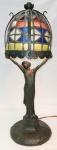 Antiga luminária de mesa, art-noveau, em pewter, na forma de figura feminina sobre pedestal, sustentando cúpula formada por mosaicos de vidros coloridos. Metal apresenta desgastes naturais causados pelo tempo e 1 vidrinho com fissura. Funcionando. Alt. 47,5 cm.