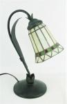 Luminária de mesa, em metal patinado, na forma de flor. Haste decorada com folha em relevo. Cúpula em vidro no tom marfim com detalhes em vidros verde e vermelho. Alt. 37 cm.