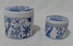 Par de caixinhas chinesas em porcelana, com formato cilíndrico, na tonalidade azul, com imagens de vários cenários chineses. Medida altura maior 8 cm e menor 5 cm.