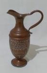 Pequena jarra em cobre, com alça e desenhos em baixo relevo com contorno na tonalidade branca. Medida altura 23 cm, largura 14 cm e diâmetro 9 cm.