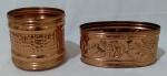 Par de cachepots em cobre, sendo, 1 redondo com diâmetro 17 cm, com detalhes em baixo relevo e 1 oval com largura 24 cm e detalhes florais em alto relevo.