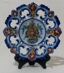 ALCOBAÇA - Prato decorativo português para parede, em cerâmica vitrificada na tonalidade azul, ano 1989, com insígnia no centro e bordas com desenhos de tema floral. Medida diâmetro 20 cm.