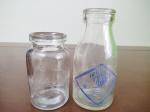 2 Pequenas Garrafas de Iogurte de Vidro sendo Best e Vigor, maior medindo 13,5 cm de altura