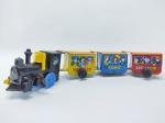 Brinquedo Locomotiva feita em Plástico acompanha por 3 Vagões em lata, medindo 29 cm de comprimento, locomotiva a corda, porem não está funcionando, necessita revisão, Obs: Faltando rodas do vagão do meio