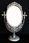 Elegante espelho de mesa em metal cinzelado ricamente trabalhado e cravejado de pedras lapidados sobre guirlandas em relevos. Medida 19x30cm.