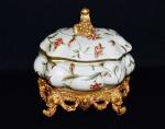 Porta objetos em porcelana com florais e pés e puxador trabalhados em material sintético. Medida 19x14x18cm.