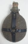 Cantil militar revestido de feltro, corpo em alumínio e presilha em couro, med.22 x 14 x 8 centímetros.