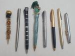 Oito canetas diversas em material diversos.