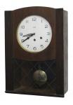 Relógio carrilhão de parede, com marca da manufatura Silco. Caixa em madeira. Mostrador em metal. Porta com vidros. Funcionando, porém necessita regulagem. Med. 55x39x19cm.