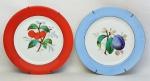 Par de prato decorativos em porcelana, decorados com pinturas de frutas ao centro em policromia. Um com aba na cor azul e outro laranja. Diam. 20 cm.