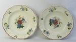 Par de pratos decorativos em faiança francesa com marca da manufatura Sarreguemines, com decoração floral em policromia. Diam. 24cm.