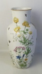 Vaso em porcelana no tom leitoso, decoração floral com borboletas e abelhas, em policromia. Base e borda com friso em dourado. Marca da manufatura na base. Alt. 31,5cm.