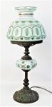 Luminária de mesa, em overlay leitoso e verde, decorada com flores e folhagens em policromia. Detalhes em dourado. Estrutura em bronze trabalhado com volutas. Funcionando. Alt. 40cm.