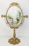 Espelho de mesa em bronze dourado, trabalhado com flores e folhagens em relevo. Espelho oval com regulagem de inclinação. Verso com placa em porcelana decorada com pintura floral em policromia. Alt. total 44,5cm.